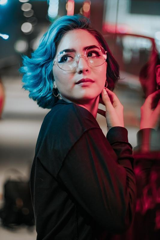 atraktivní žena s brýlemi v tmavém městě