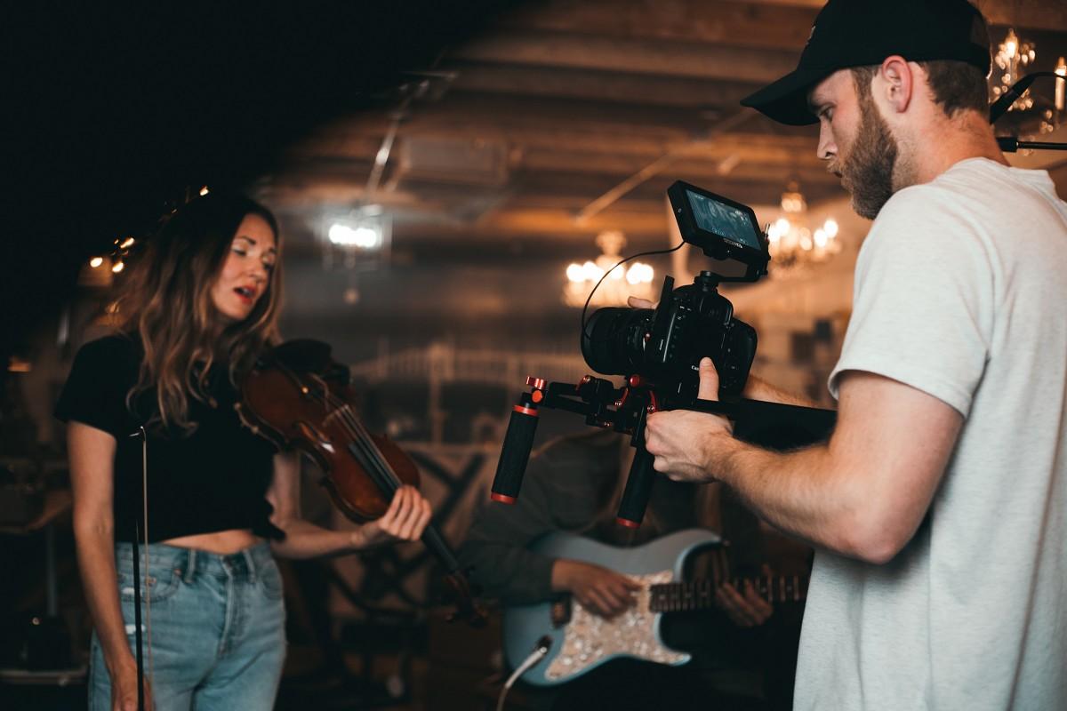 muž natáčející koncert na fotoaparát se stabilizátorem